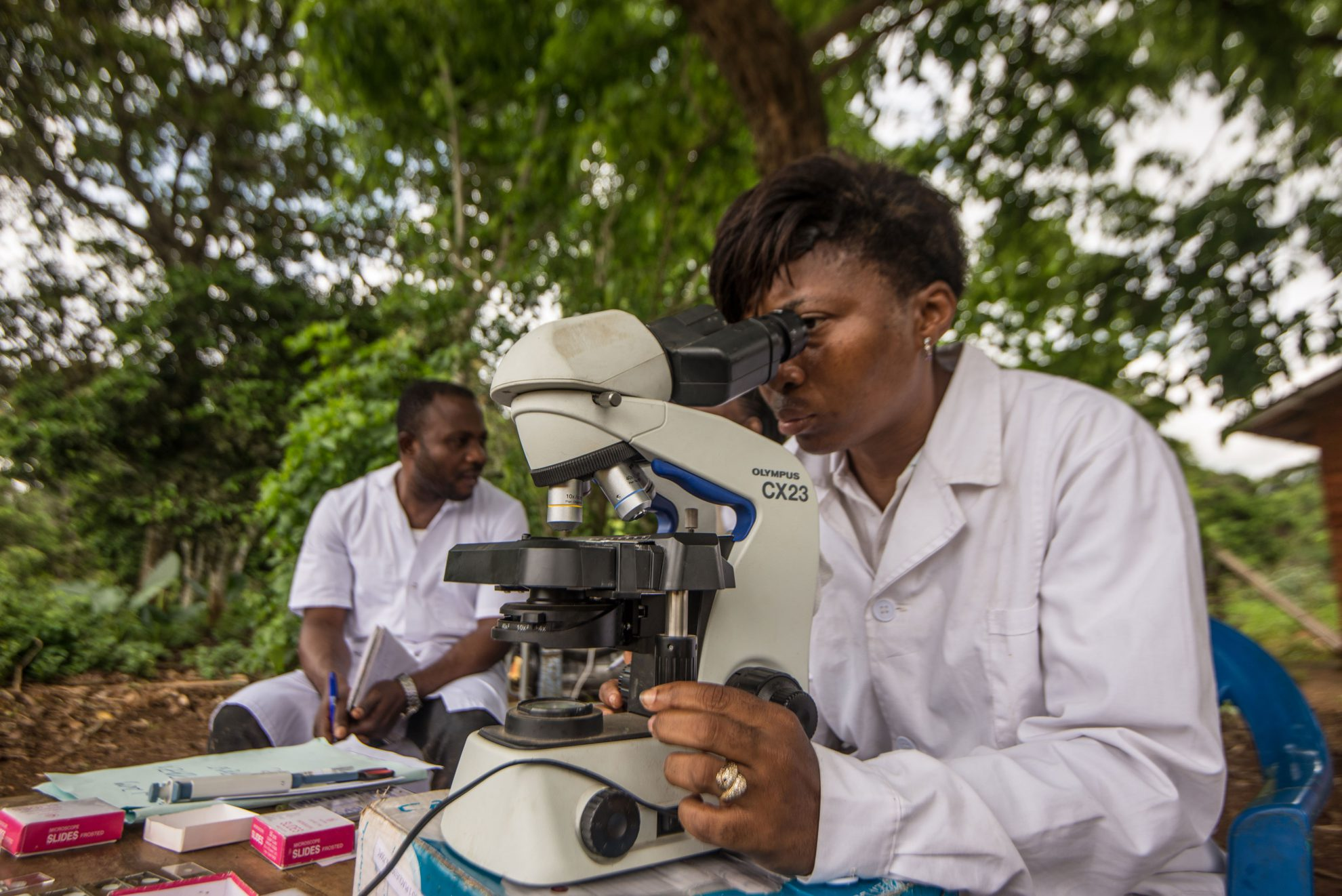 Researcher looks at samples through microscope to detect river blindneess